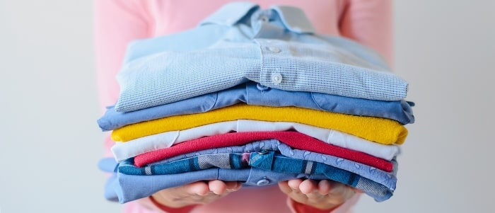 girl-holding-pile-of-washed-and-ironed-clothes
